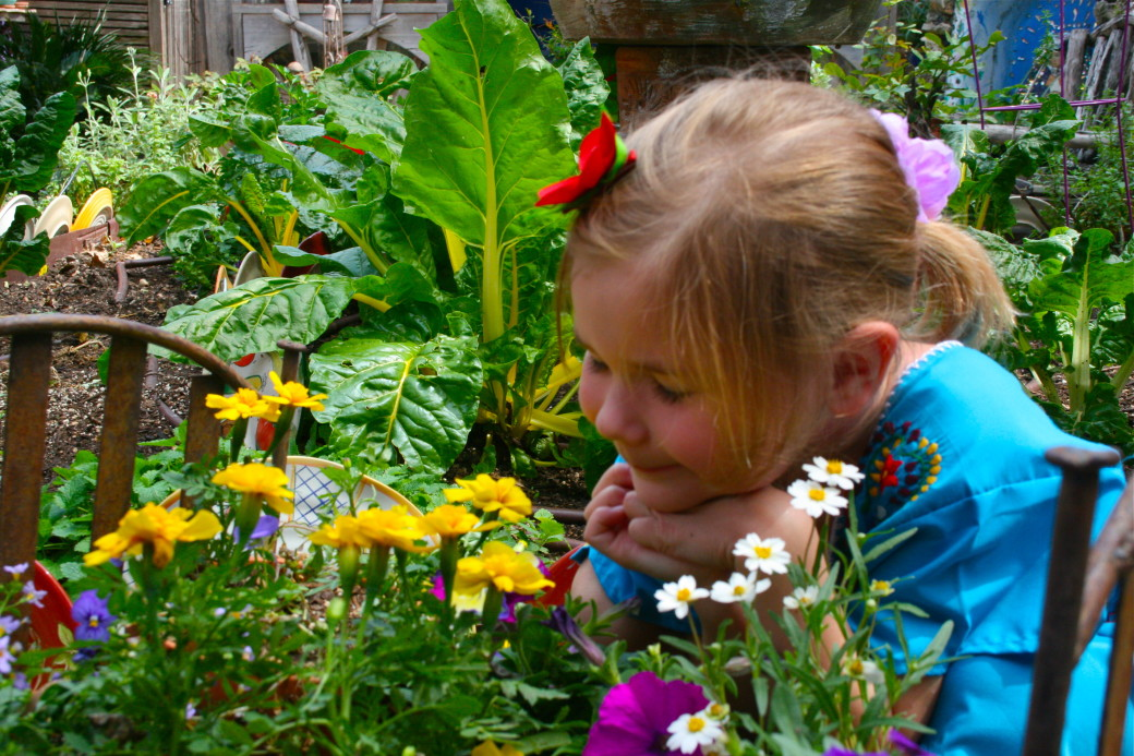 girl in garden flower bed smelling flowers